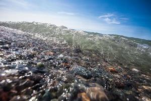 strandkust met stenen en blauwe hemel foto