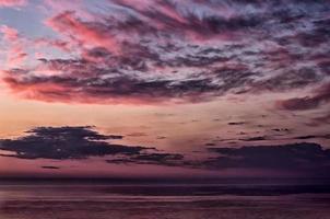 bewolkte hemel bij zonsopgang boven de zee