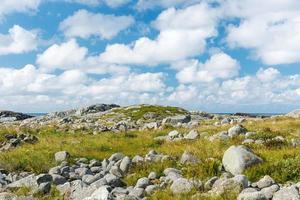 steenachtig landschap met blauwe lucht en witte wolken.
