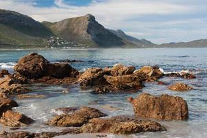 rotsachtig zeegezicht met bergen en bewolkte luchten