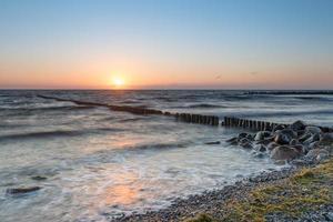 rotsen over zee surfen in de avond foto