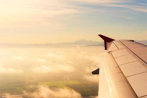 vleugel van het vliegtuig op gouden hemelachtergrond