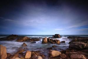 golven die op rotsachtige kust in de zonsondergang breken