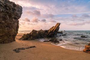 rotsen op zee in de vroege ochtend met rustige golven foto