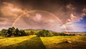 dubbele regenboog over landschap bij zonsondergang