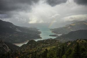 schilderachtig uitzicht vanaf de berg naar het meer en de regenboog