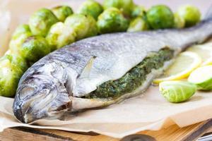 twee vissen, forel gevuld met groene kruidensaus, spruitjes