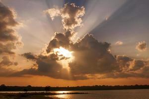 zon gaat door wolken bij zonsondergang foto