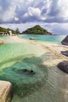 jonge kerel zwemmen binnen vis cricle kristal water tropisch strand foto