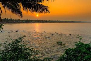 oranje zon bij zonsopgang boven de zee en het palmblad foto