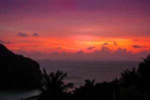 roze levendige tropische zonsondergang over water - Thailand foto