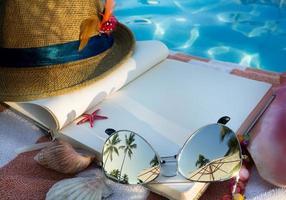 kunststrohoed, boek en zonnebril op het strand