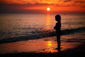 jongen op de zee bij zonsondergang