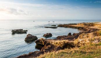 rotsachtige kust en zie met vissers foto