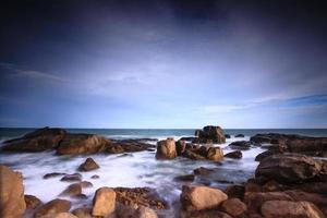 golven die op rotsachtige kust in de zonsondergang breken foto