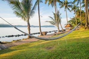 uitzicht op gezellige stro hangmat op het tropische witte strand foto