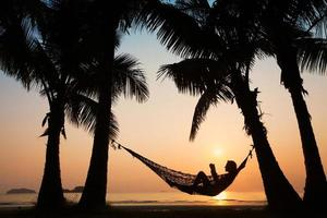zonsondergang in hangmat op het strand foto