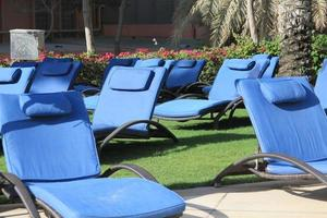 ligstoelen naast het zwembad of het strand van een resort foto
