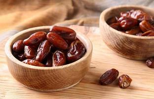 vruchten datums in houten kom op tafel foto