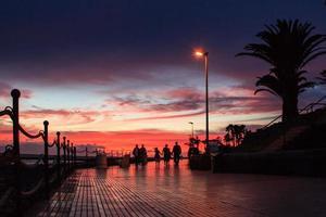strandboulevard playa del duque bij zonsondergang foto