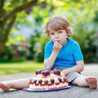 kleine jongen viert zijn verjaardag met grote taart foto