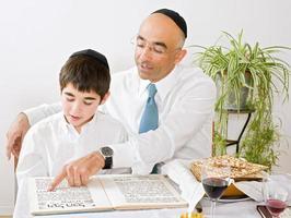een vader en zoon die Pesach vieren en lezen foto