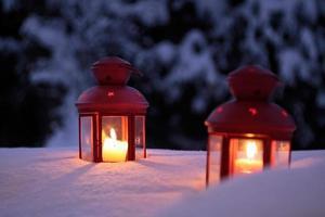 twee brandende lantaarns in de sneeuw