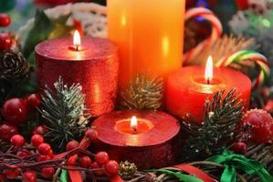 close up van feestelijke brandende kaarsen met naaldboom en decoraties foto