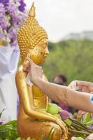 water gieten en verguld Boeddhabeeld in songkran festival trad