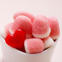 roze gelei of marshmallows met suiker in kom