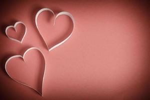 drie harten van wit papier liggend op een rode achtergrond foto