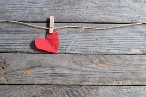 rood hart opknoping op de waslijn. op oude houten achtergrond. foto