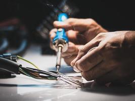 elektricien die een soldeerbout gebruikt om de draden met de metalen pin te verbinden