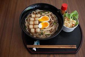Japanse tarwenoedel, udon-noedel op houten lijstachtergrond foto