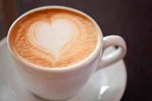 koffie in een kop en schotel met hartvormig schuim foto