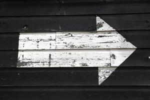 witte pijl geschilderd op een zwarte houten schuurmuur foto