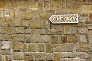 eenrichtingspijl op oude stenen muur