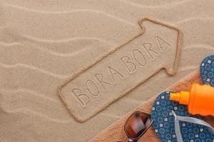 Bora Bora aanwijzer en strandaccessoires liggend op het zand