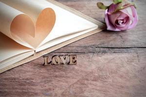 hartvorm gemaakt van pagina's met bloem op oud hout