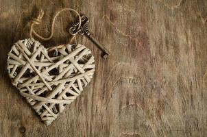 handgemaakt rieten hart met de sleutel op een houten sokkel foto