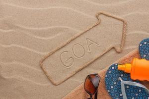 goa aanwijzer en strandaccessoires liggend op het zand