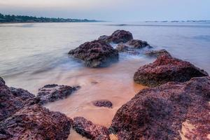 de huidige zeegolven en prachtige stenen aan de kust foto