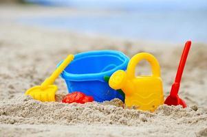 plastic kinderspeelgoed op het zandstrand foto