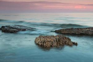 zee en stenen na zonsondergang foto