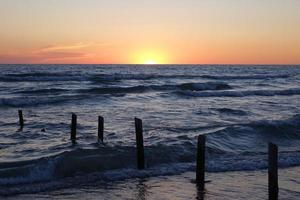 palen in het water onder een zonsondergang