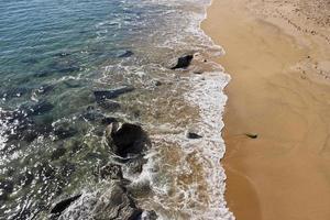 golf die het zand aan de kust bevochtigt. foto