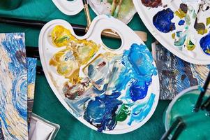 penselen, palet, verf en water op tafel