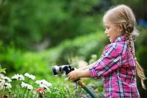 meisje bloemen in tuin met slang water geven