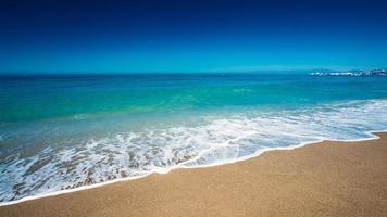 zachte zee oceaan golven wassen over gouden zand achtergrond foto
