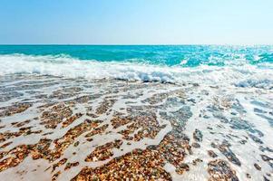 helder zeewater en kiezelstrand foto